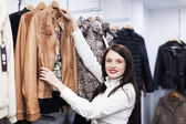 Fermale customer choosing jacket at store — Zdjęcie stockowe