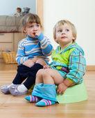 Two children  sitting on chamber pots  — Stockfoto