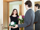 Girl giving flowers and present — Stock Photo