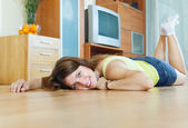 Woman lying on hardwood floor  — Stock Photo