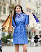 Smiling woman in blue coat with purchases — Stock Photo
