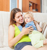 Smiling  woman with toddler on sofa — Stock Photo