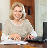 Smiling mature woman with laptop — Stock Photo