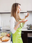 Woman  with cakes and tea in  kitchen — Stock Photo