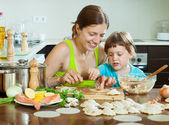 Woman with   child makes Fish dumplings — Stock Photo