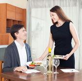 Woman prepares dinner for man — Stock Photo