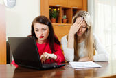 Unhappy women looking  documents with laptop  — Stock Photo
