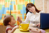 Businesswoman feeding baby — Stock Photo