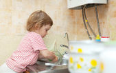 Baby girl  washes dishes — Stock Photo
