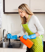 Woman  cleaning pipe   in kitchen — Stockfoto