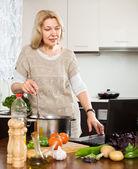 äldre kvinna matlagning soppa — Stockfoto