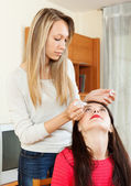 woman dripping eye drops to girlfriend  — Stock Photo