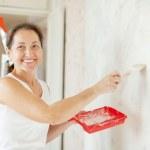 Постер, плакат: Woman makes repairs at home