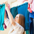 Housewife drying clothes on clothes-line — Stock Photo #47124387