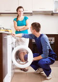 Woman watching as young  worker repairing washing machine — Stock Photo