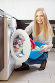Woman loading   the washing machine — Stock Photo