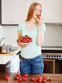 Long-haired woman eating strawberries  — Stock Photo