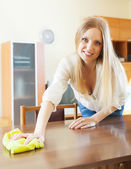 Woman wiping the dust from table — Foto Stock