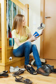 Long-haired blonde woman cleaning footwear — Stock Photo