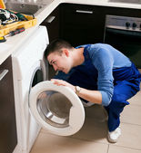 Repairman in uniform repairing washing machine — Stock Photo