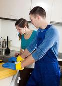 Plumber repairing kitchen sink for  woman — Stock Photo