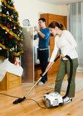 Happy adult couple doing housework — Stock Photo