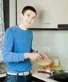 Guy pouring dough  in frying pan — Stockfoto