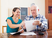Man with pensive mature wife fills in questionnaire — Stock Photo