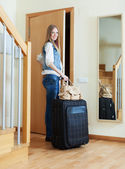 Woman with suitcase near door   — Stock Photo