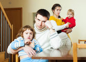 Young couple with children after quarrel at home — Stock Photo