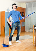 Happy young  guy  with dustpan and brush — Stock Photo