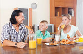 Homem e mulher com rapaz tomando café da manhã — Fotografia Stock