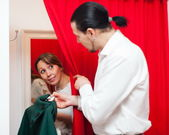Couple trying coat in fitting-room — Stock Photo