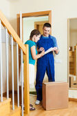 Delivery man in uniform delivered a parcel to young  woman at ho — Stock Photo