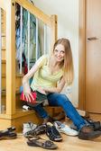 Happy blonde woman cleaning footwear  — Foto Stock