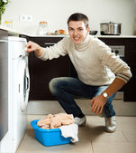 Guy putting clothes into washing machine — Stock Photo