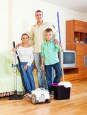 Retrato de família feliz com equipamentos de limpeza — Fotografia Stock