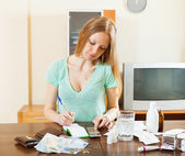 Serious woman counting the cost of medications — Stock Photo