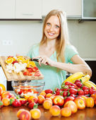 Woman cooking fruit salad — Stock Photo