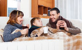 Happy family    warming near warm radiator — Stock Photo