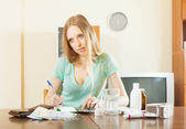 Sad blonde woman with medications and money — Stock Photo
