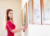 Smiling  woman hanging  picture  on wall — Stock Photo