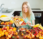 Ordinary long-haired  girl cooking fruit salad — Stock Photo