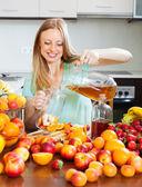积极的金发女孩,浇注新鲜的饮料 — 图库照片