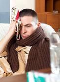 Sad  man having headache holding towel on head — Stock Photo