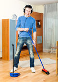 Happy guy   cleaning  in living room — Stock Photo