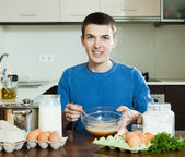 Man cooking scrambled eggs — Stock Photo