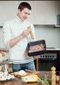 Ordinary man cooking meat with  mushrooms and potatoes — Stock Photo