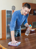 Guy cleaning furniture with cleanser and rag at living room — Foto Stock