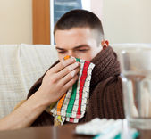 Sick man in plaid uses handkerchief — Stock Photo
